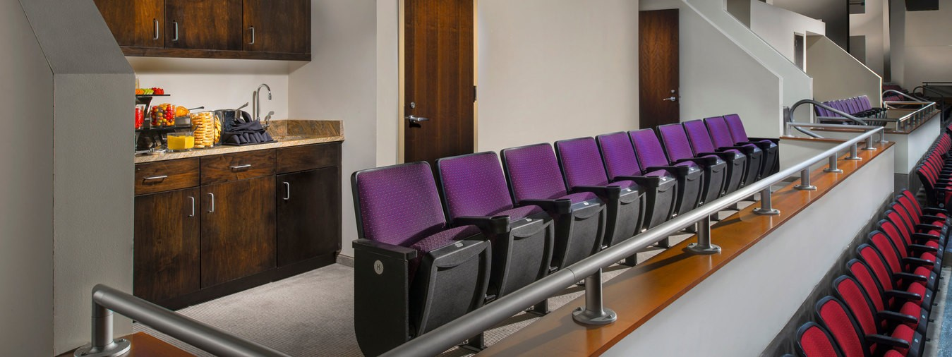 A row of theater-style seats in a private box with a kitchenette in the Event Center at Turning Stone